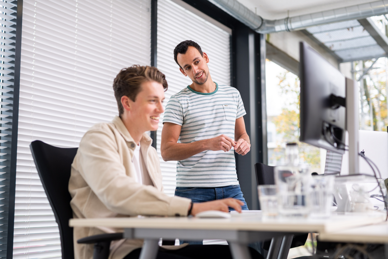 Twee collega's bespreken een bericht op het intranet bij Netvlies